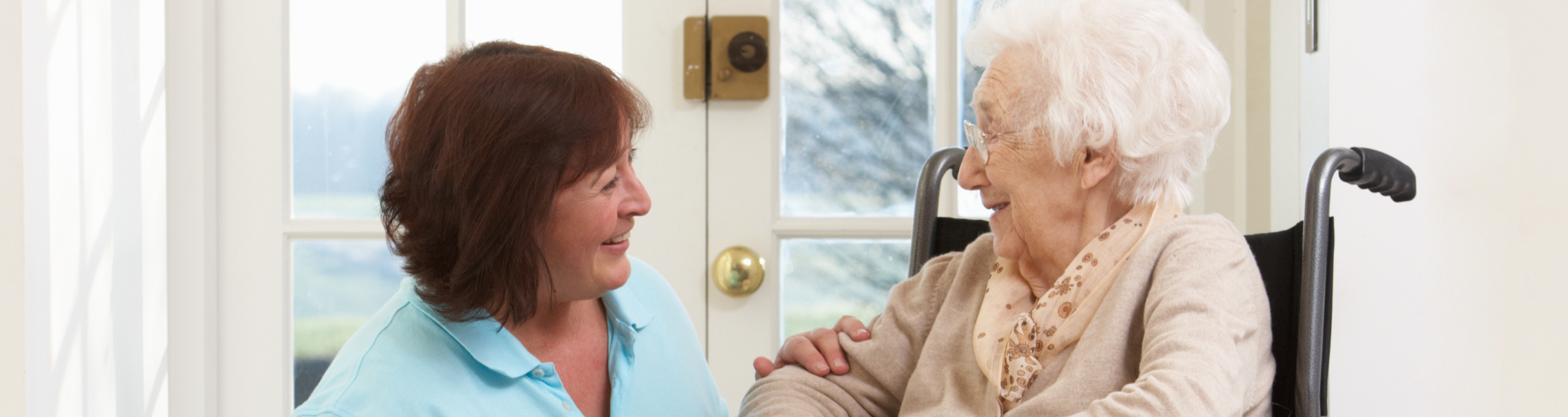 Elderly woman in a wheelchair speaking with a caregiver