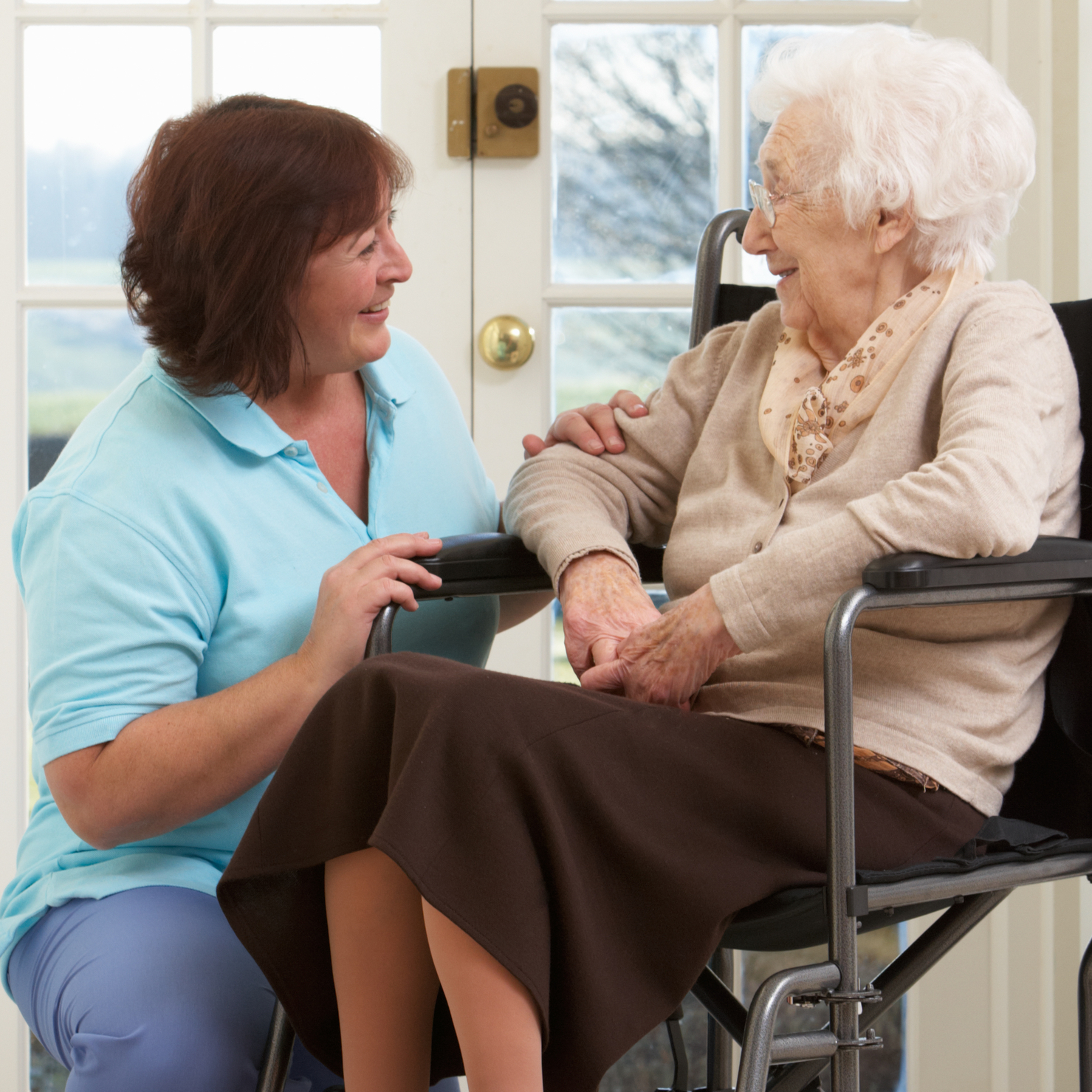 Elderly woman in wheelchair speaking with caregiver
