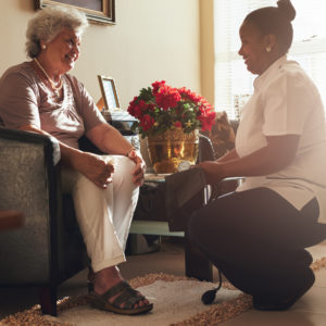 Female nurse visiting senior patient for checking blood pressure
