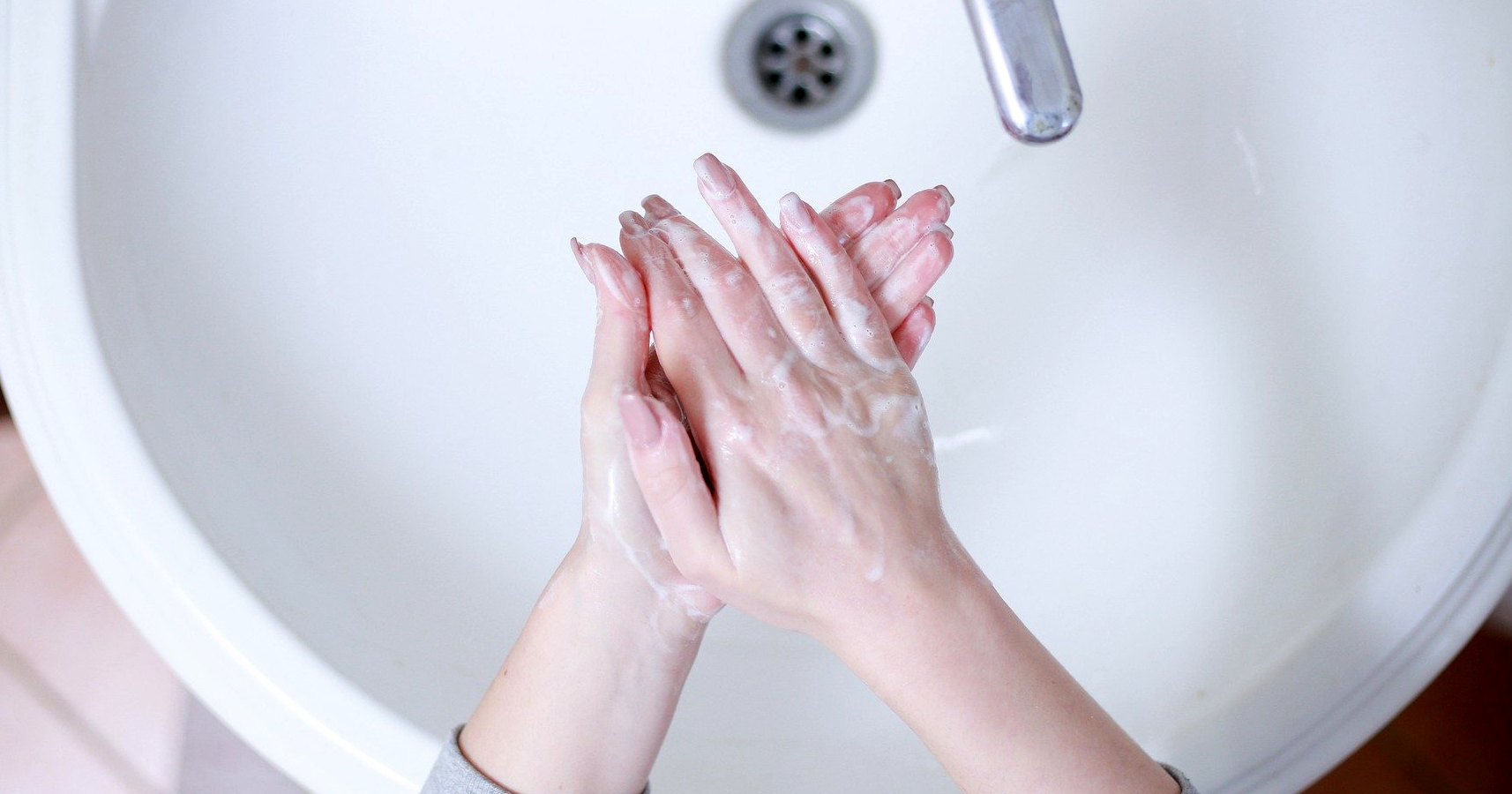 Top view of sink and woman's hands washing