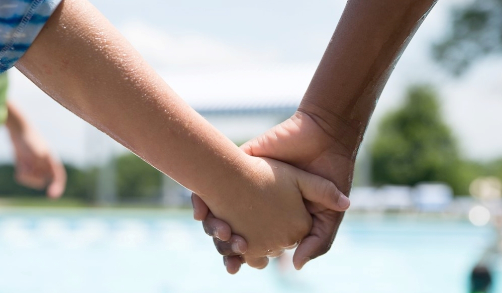Light and dark skinned hands hold each other full frame in front of a pool