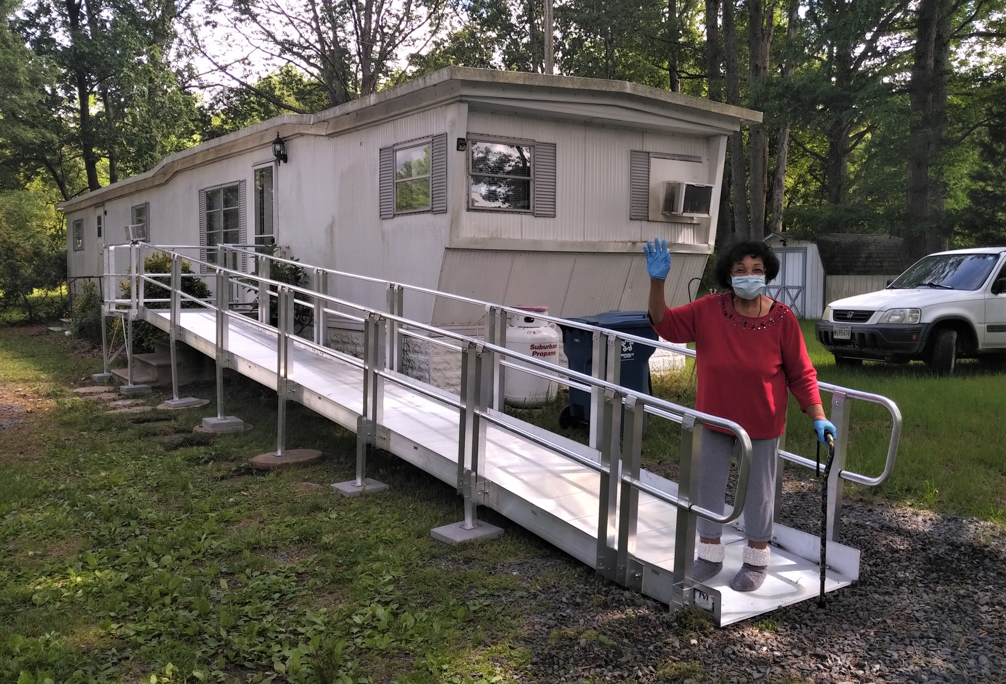 A mobile home with an new ramp installed and the homeowner on it waving