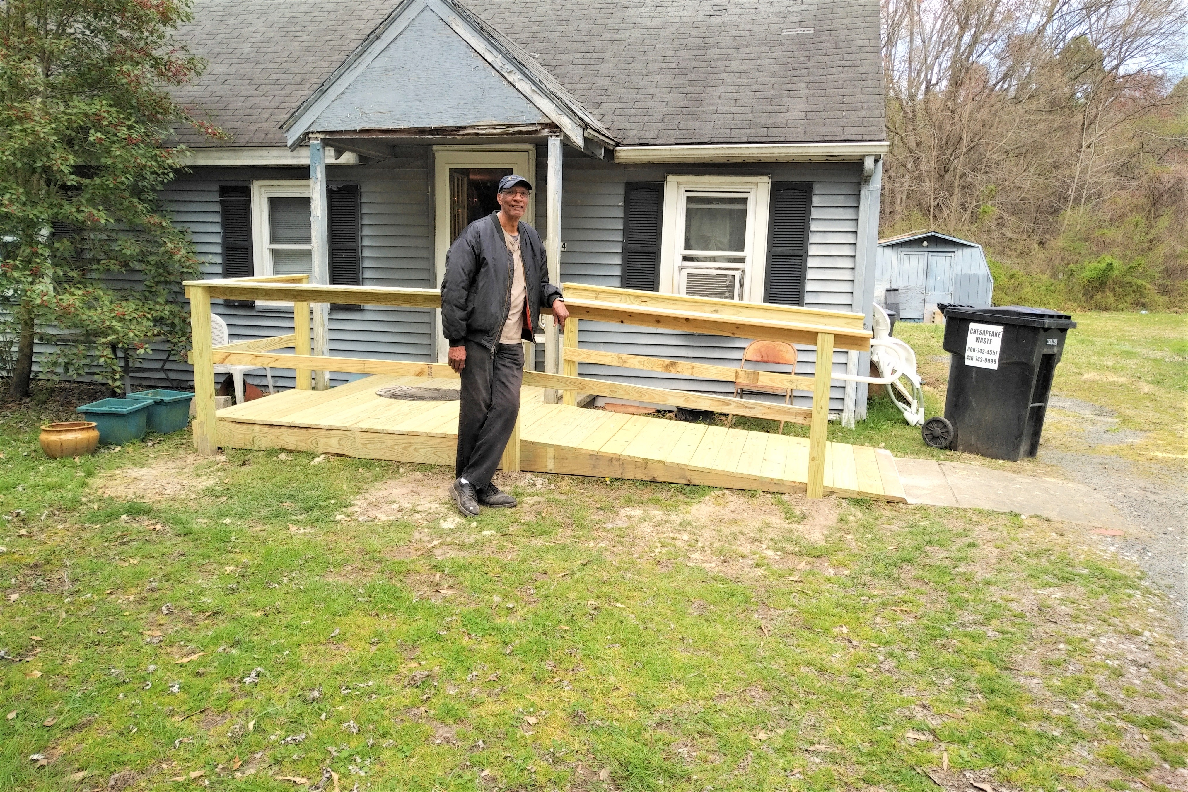A man standing proudly in front of a newly built wooden ramp