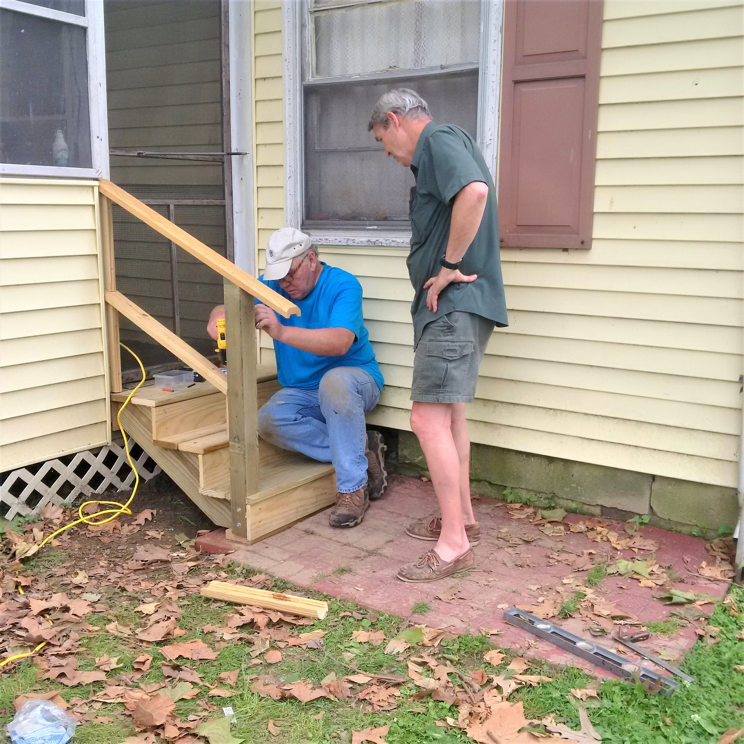 Two men building wooden steps