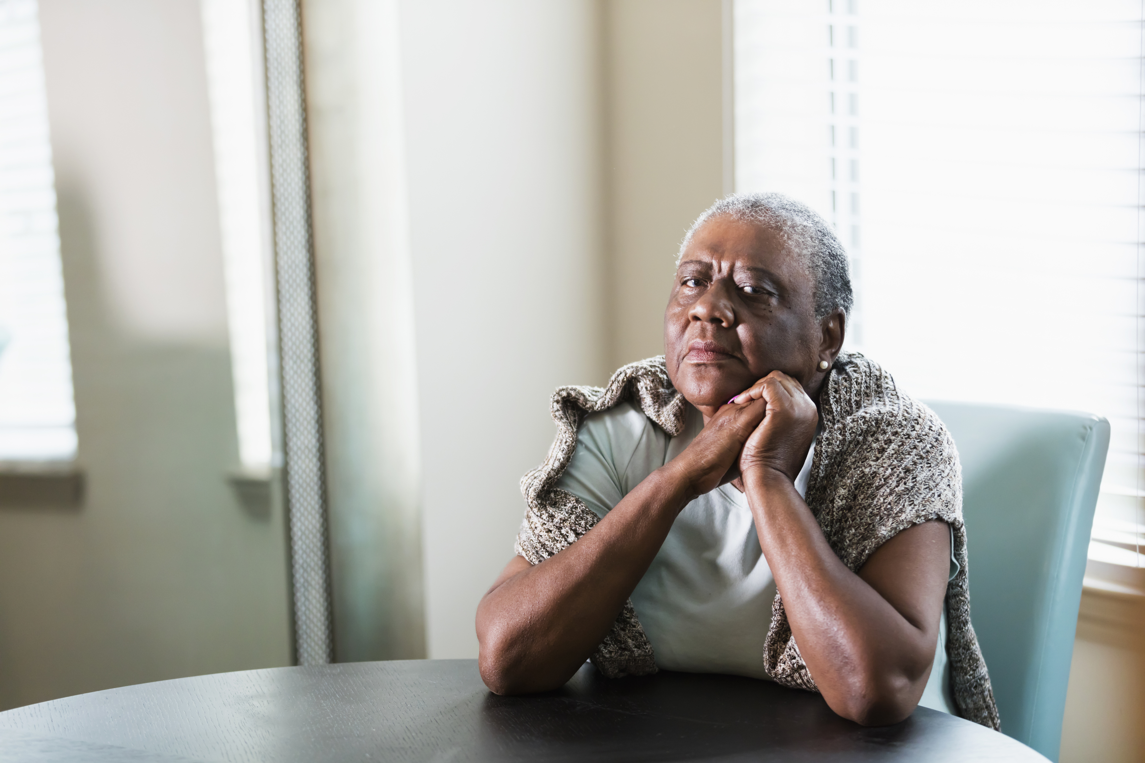 A lonely senior African-American woman in her 70s sitting at home at a table by a window. She is looking at the camera with a serious expression, elbows on the table and hands clasped.