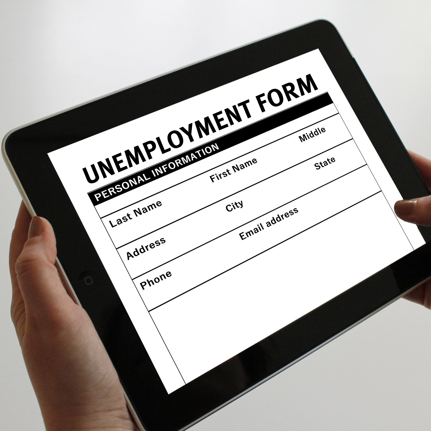 hands holding a tablet with an unemployment form on it