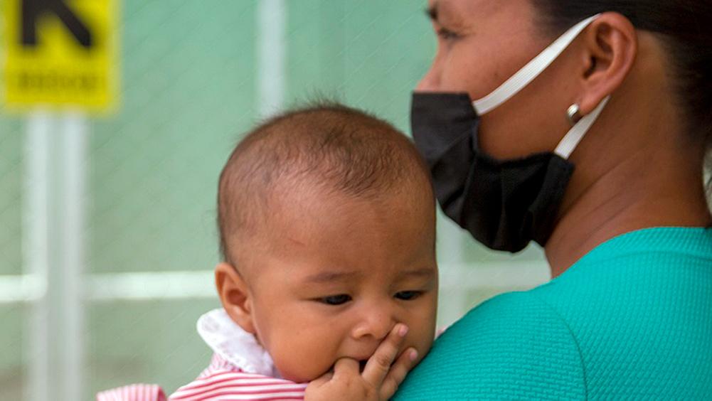 masked mother holds infant